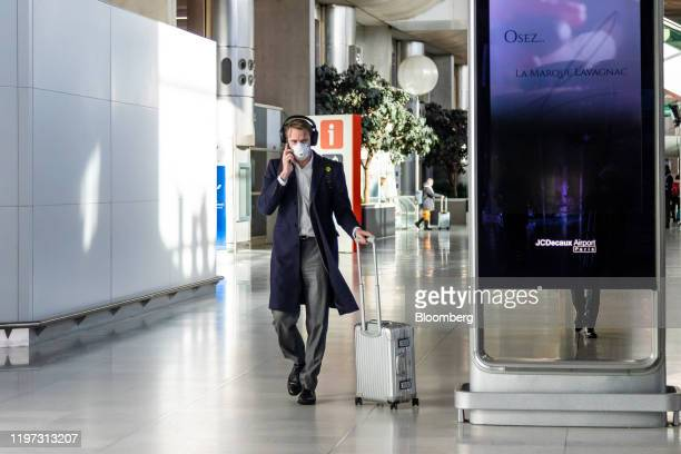 A passenger in a protective face mask wheels luggage at Charles de Gaulle airport operated by Aeroports de Paris in Roissy France on Tuesday Jan 28...