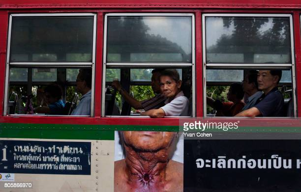 A passenger in a public bus in Bangkok peers out of a window above a particularly gruesome and shocking antismoking advertisement In recent years the...