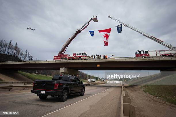 A passenger in a truck waves back as firefighters welcome residents home in Fort McMurray Alberta Canada on Wednesday June 1 2016 Residents began...
