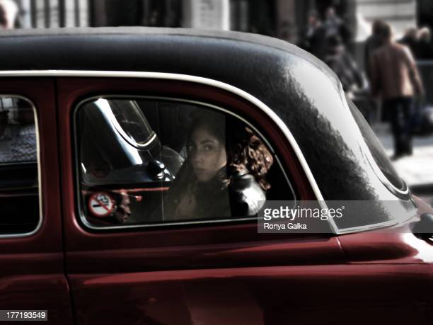 CONTENT] Passenger in London black cab woman sitting in traffic in maroon taxi