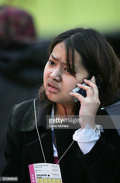 A passenger injured in a commuter train wreck talks on her cell phone in the triage area January 26 2005 in Glendale California The twotrain wreck...
