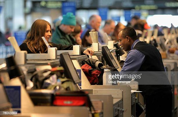 A passenger is attended to by a United Airlines representative the day before Thanksgiving at the Denver International Airport on November 21 2007 in...