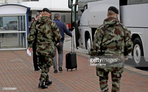 Passenger is escorted to a bus to be taken to the Crowne Plaza hotel for quarantine on March 29, 2021 in Dublin, Ireland. Last week, Ireland started...