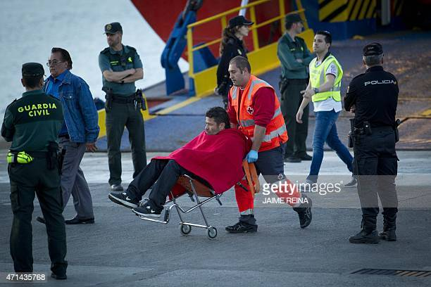 A passenger is pushed along by a member of the Red Cross apon disembarking from a ship in the port of Palma de Mallorca on 2015 after the passenger...