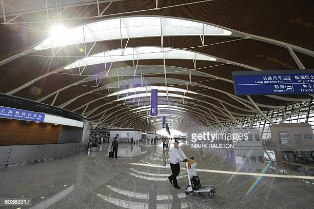 A passenger is seen in the main departures hall of the new terminal two at the Pudong International Airport in Shanghai on March 26 2008 The new...