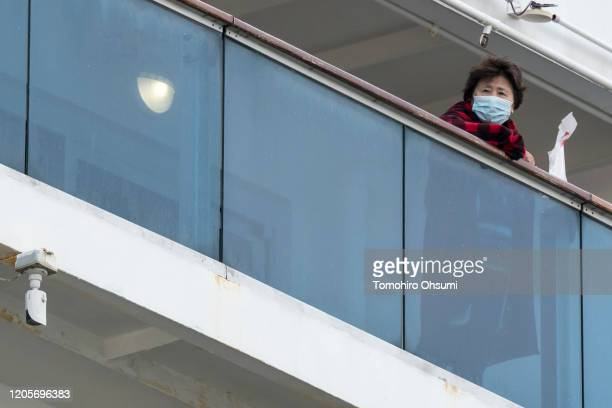 Passenger is seen on a balcony of the Diamond Princess cruise ship as the ship arrives at Daikoku Pier where it is being resupplied and newly...