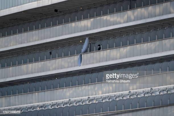 A passenger is seen on a balcony of the quarantined Diamond Princess cruise ship docked at Daikoku Pier on February 19 2020 in Yokohama Japan About...