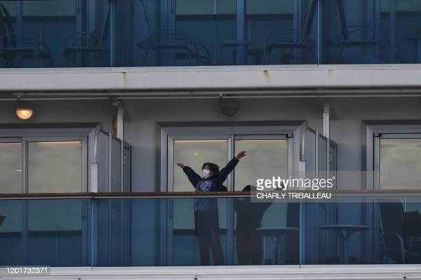 A passenger is seen on the balcony of the Diamond Princess cruise ship in quarantine due to fears of the new COVID19 coronavirus at the Daikoku Pier...