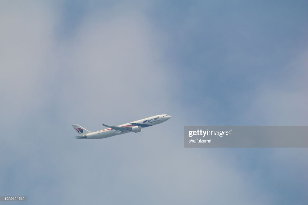 Passenger jet air plane from Malaysia Airlines flying on blue sky over white clouds. : Stock Photo