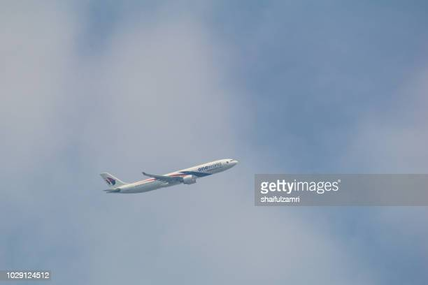 passenger jet air plane from malaysia airlines flying on blue sky over white clouds. - shaifulzamri fotografías e imágenes de stock