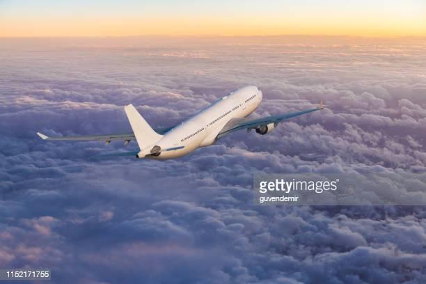 aereo a reazione passeggeri che vola sopra le nuvole al tramonto - aeroplano foto e immagini stock