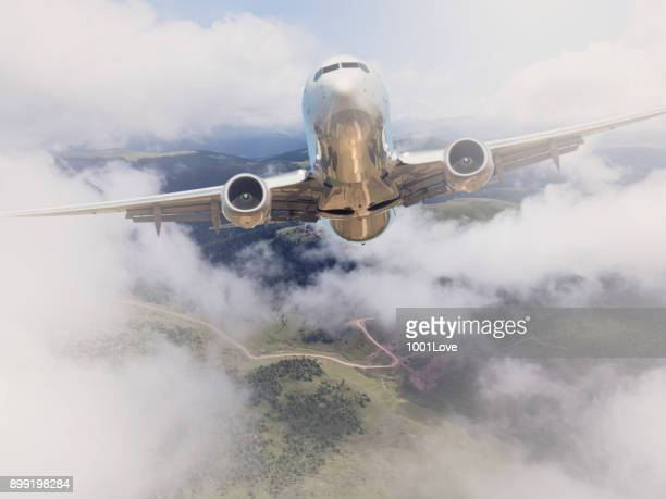 Passenger jet airplane flying above clouds