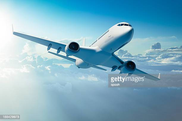 passenger jet airplane over clouds - aeroplane stock photos and pictures