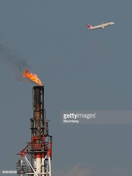 A passenger jet flies over a TonenGeneral Sekiyu KK oil refinery in Kawasaki City Kanagawa Prefecture Japan on Wednesday Nov 26 2008 Japan's crude...