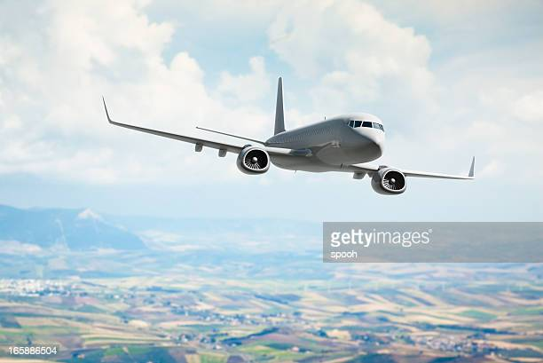 Passenger jet flying over fields