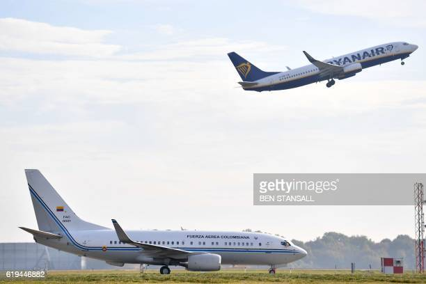 A passenger jet operated by Irish airline Ryanair takes off behind the President of Colombia's Air Force plane on the tarmac as Colombian President...