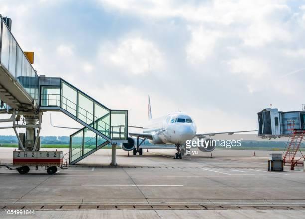 passenger jet parking at airport tarmac - airport tarmac stock pictures, royalty-free photos & images