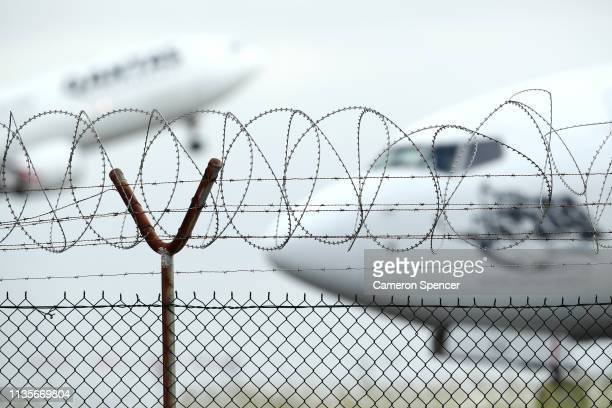 A passenger jet taxis past a security fence at Sydney Airport on March 14 2019 in Sydney Australia The Civil Aviation Safety Authority has suspended...