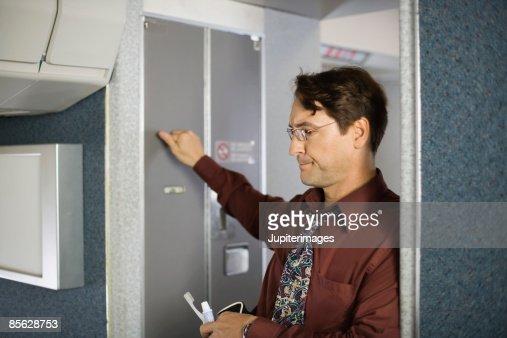 Passenger Knocking On Lavatory Door On Airplane Stock ...