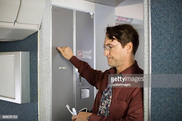 Passenger knocking on lavatory door on airplane