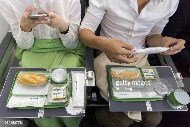 A passenger left uses a smartphone to take a photograph of an inflight meal served on board an Airbus SE A321 Neo aircraft operated by FLC Group...