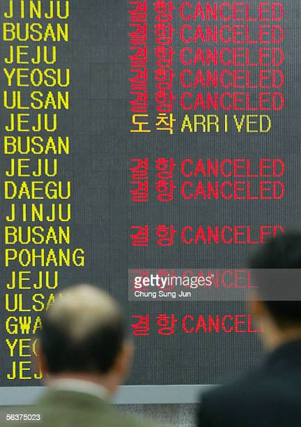 Passenger look at the flight information boards at Gimpo Airport December 8 2005 in Seoul South KoreaUnionised pilots at Korean Air went on strike...