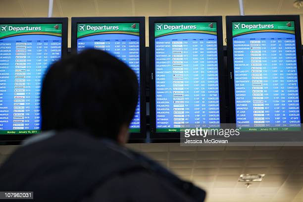 A passenger looks at a departure screen of cancelled flights at Atlanta HartsfieldJackson International Airport after a snow storm on January 10 2011...