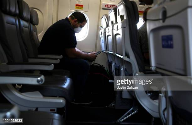 Passenger looks at his phone while waiting aboard a United Airlines plane before taking off from George Bush Intercontinental Airport on May 11, 2020...