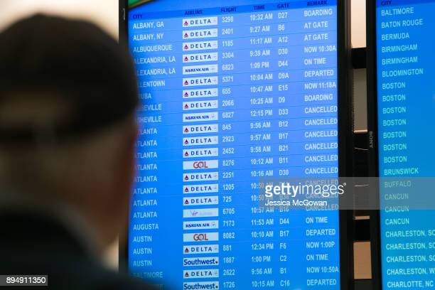 A passenger looks at the departure board for the status of flights at HartsfieldJackson Atlanta International Airport on December 18 2017 in Atlanta...