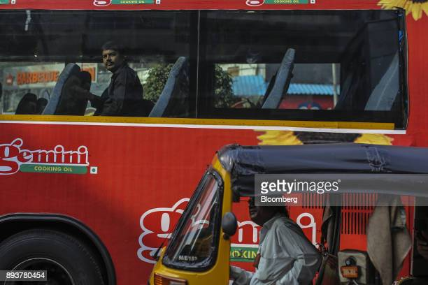 A passenger looks out from a bus as an auto rickshaw drives along a road in Mumbai India on Friday Dec 15 2017 India's inflation surged past the...