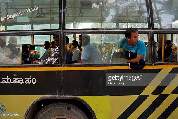 A passenger looks out of a bus window as it travels through the Brigade Road shopping area in central Bangalore India on Wednesday Jan 8 2014...