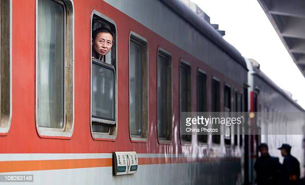 A passenger looks out of a cabin window after boarding at the Wenzhou Railway Station on January 23 2011 in Wenzhou of the Zhejiang Province China...