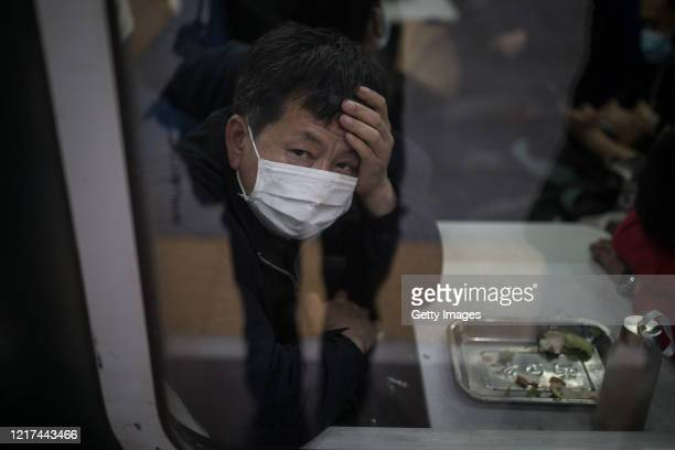 Passenger looks out of the window while the train from Xi'an to Guangzhou stops in Wuhan on April 8,2020 in Wuhan, Hubei Province, China. The Chinese...