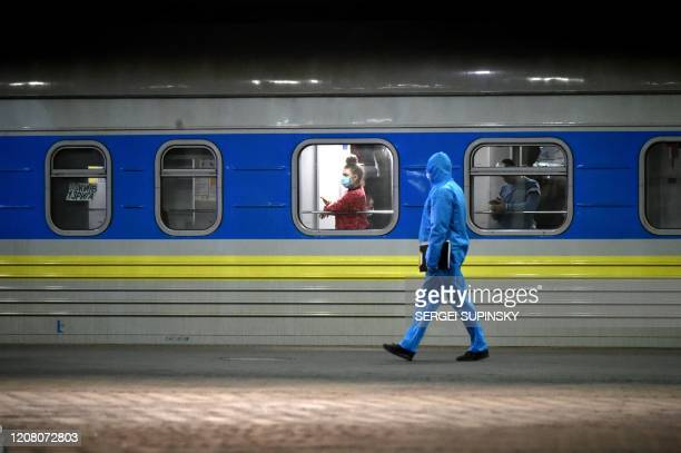 TOPSHOT A passenger looks out the window as a medical worker walks past her carriage of a train with Ukrainians evacuated from Riga at a railway...
