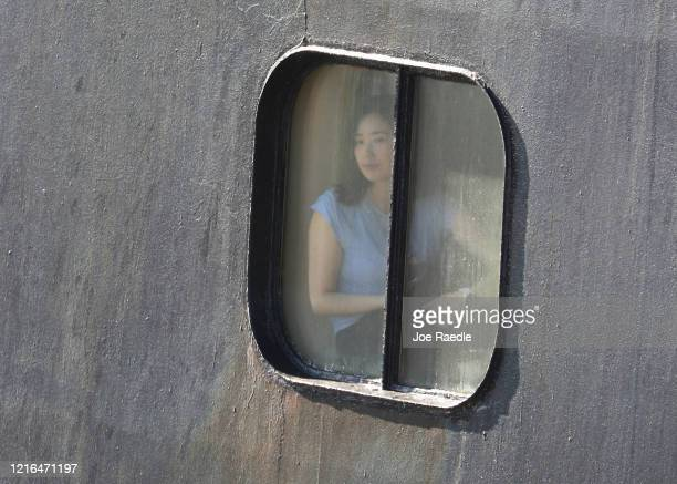 A passenger looks out the window as the Rotterdam cruise ship arrives at Port Everglades on April 02 2020 in Fort Lauderdale Florida The Holland...