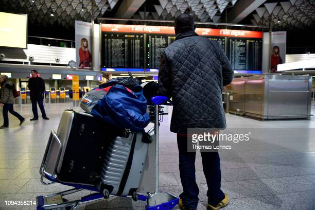 Passenger looks to the departures board showing cancelled flights at Frankfurt Airport during a strike by security personnel on January 15, 2019 in...