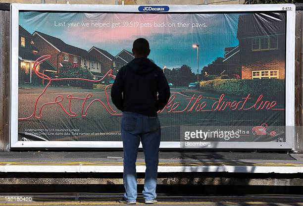 A passenger looks toward an advertisement for pet insurance from Direct Line Insurance Group Plc in this arranged photograph at Maryland rail station...