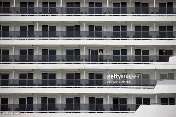 Passenger loosk out from her balcony on board the MSC Virtuosa cruise ship as it prepares to set sail following the easing of Covid-19 restrictions...