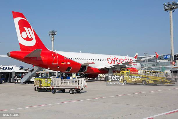 Passenger luggage transfer vehicles sit beside an Airbus A320200 passenger plane operated by Air Berlin Plc outside terminal 2 at Frankfurt Airport...