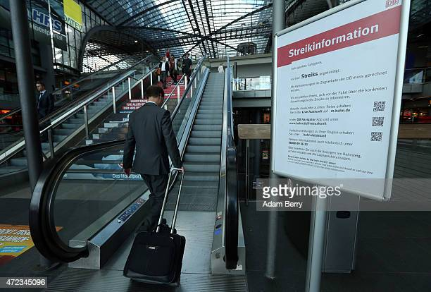 Passenger of German state rail carrier Deutsche Bahn passes a sign warning of strikes at the Hauptbahnhof, or main train station, during a week-long,...