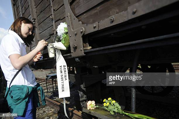 A passenger of the 'Train of Remembrance' lights a candle by a ribbon bearing the name of radical pacifist and Nobel Peace Prize winner Bertha von...