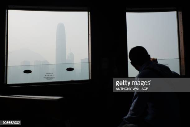 A passenger on a Star Ferry looks out of a window as smog engulfs commercial buildings in Hong Kong on January 22 2018 Hong Kong's famous skyline was...