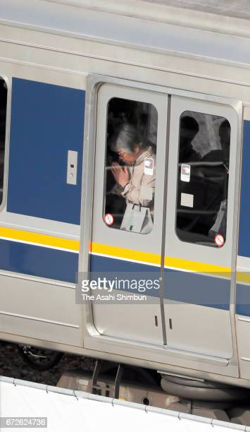 A passenger on a train prays towards the accident site on the twelveth anniversary of the train derailment accident on April 25 2017 in Amagasaki...