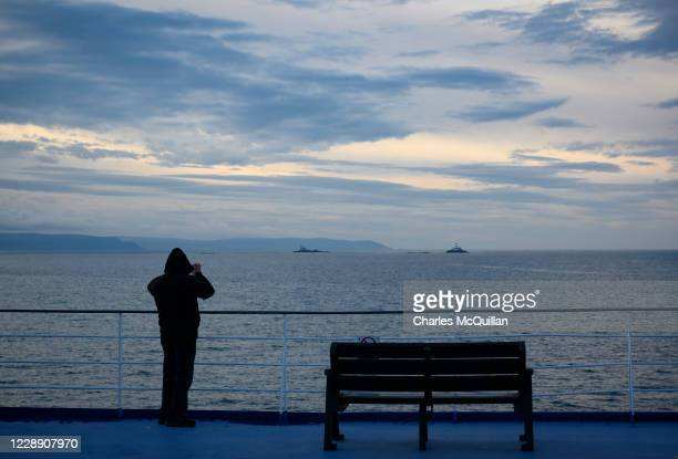 Passenger on board the Cairnryan to Larne ferry between Northern Ireland and Scotland takes a photograph as he arrives at the port of Larne on...