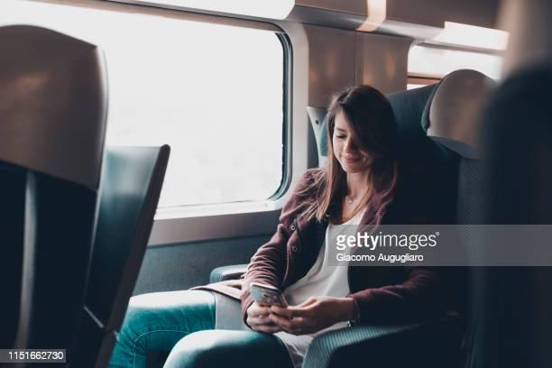 a passenger on tgv train watching her smartphone, paris, france, europe - tgv photos et images de collection