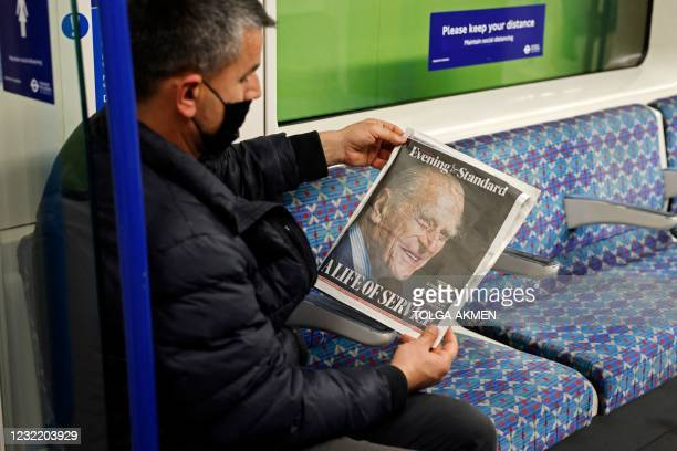 Passenger on the London Underground looks at the front page of the Evening Standard, London's daily free newspaper showing a cover photograph of...