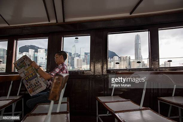 A passenger on the Star Ferry reads the newspaper with the towering Central skyline behind on June 6 2014 in Hong Kong The ferry which connects Hong...