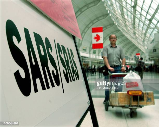 A passenger passes a SARS information board at Pearson International Airport in Toronto 28 May 2003 Over 5000 Toronto residents have been placed in...