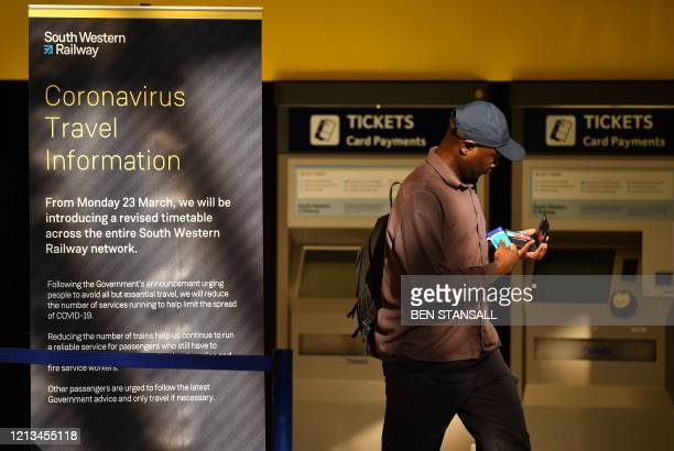 Passenger passes ticket machines and a sign, alerting passengers and commuters to a revised timetable due to the COVID-19 pandemic, at Clapham...