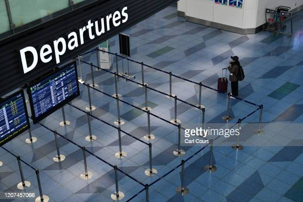 A passenger pauses next to an empty departure gate at Haneda Airport on March 17 2020 in Tokyo Japan Haneda Airport the fourth busiest in the world...